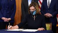 Ketua DPR Nancy Pelosi menandatangani dokumen pemakzulan Presiden Donald Trump di Capitol Hill, Washington, Amerika Serikat, Rabu (13/1/2021). Ada 10 anggota Partai Republik yang ikut mendukung pemakzulan Donald Trump. (AP Photo/Alex Brandon)