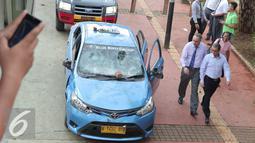 Sejumlah pekerja melihat kondisi mobil taksi yang hancur akibat dirusak oleh ojek online di Jakarta, Selasa (22/3). Kedua transportasi tersebut saling serang dan menswiping satu sama lain. (Liputan6.com/Angga Yuniar)