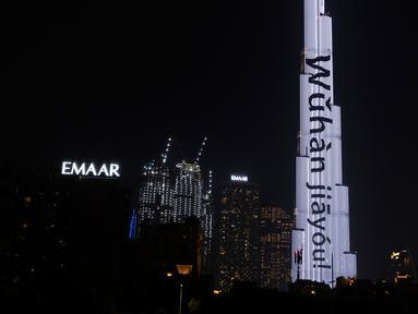 Burj Khalifa diterangi dengan slogan-slogan 'Wuhan jiayou' yang berarti 'Wuhan, semangat' di pusat Kota Dubai, Uni Emirat Arab (UEA), Minggu (2/2/2020). Hal tersebut untuk memberi semangat kepada China dalam perang melawan virus corona. (Xinhua/WAM)