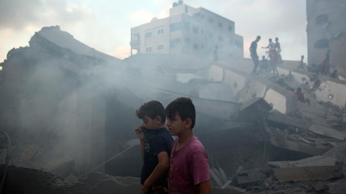 Dua remaja berada di puing-puing bangunan yang hancur akibat serangan udara Israel di Kota Gaza, Palestina, (9/8). Israel dan Hamas telah berperang tiga kali sejak Hamas menguasai Gaza pada 2007. (AP Photo/Khalil Hamra)