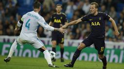 Striker Tottenham, Harry Kane, berusaha melewati bek Real Madrid, Sergio Ramos, pada laga Liga Champions di Stadion Santiago Bernabeu, Madrid, Selasa (17/10/2017). Kedua klub bermain imbang 1-1. (AP/Paul White)