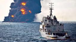Sebuah kapal penyelamat berlayar di dekat kapal tanker minyak Iran yang terbakar di Laut Cina Timur (14/1). Kapal tanker nahas tersebut sedang berlayar menuju Korea Selatan sebelum bertabrakan dengan sebuah kapal kargo. (Ministry of Transport via AP)
