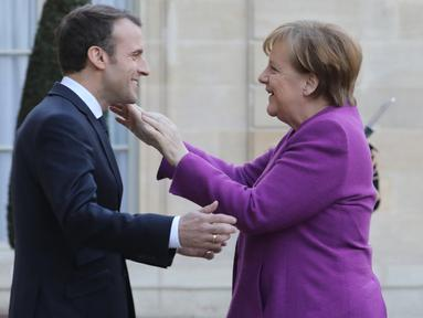 Presiden Prancis Emmanuel Macron (kiri) menyambut Kanselir Jerman Angela Merkel saat tiba di Istana Presiden Eylsee di Paris (16/3). Pertemuan tersebut untuk membahas reformasi Uni Eropa. (AFP Photo/Ludovic Marin)
