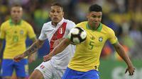 Gelandang Brasil, Casemiro, berebut bola dengan striker Peru, Paolo Guerrero, pada laga final Copa America 2019 di Stadion Maracana, Rio de Janeiro, Minggu (7/7). Brasil menang 3-1 atas Peru. (AFP/Carl De Souza)