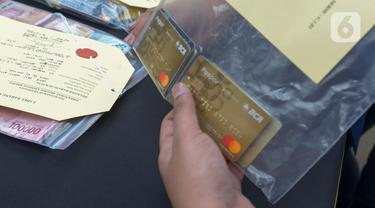Petugas memperlihatkan hasil kejahatan sindikat pembobolan rekening lewat kartu ATM saat konferensi pers di Polda Metro Jaya, Jakarta, Selasa (10/3/2020). Polisi menangkap empat pelaku, ARS (26), DN (56), MR (33), dan H (19) dan satu tersangka berinisial M masuk DPO. (merdeka.com/Imam Buhori)