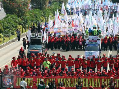 Massa buruh dan pekerja dari berbagai daerah mulai memadati Jalan MH Thamrin, Jakarta, dalam peringatan May Day, Senin (1/5). Mereka mengibarkan bendera organisasi buruh dan membentangkan spanduk di sepanjang perjalanan. (Liputan6.com/Johan Tallo)