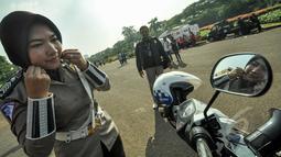 Seorang polwan saat membetulkan jilbabnya sebelum bertugas di pelataran Silang Monas, Jakarta, Jumat (27/3/2015). Polwan di seluruh Indonesia akhirnya diperbolehkan mengenakan jilbab. (Liputan6.com/Faizal Fanani)