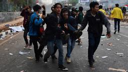 Sejumlah mahasiswa menggotong rekan mereka yang terluka saat demonstrasi menolak pengesahan RUU KUHP dan revisi UU KPK di depan Gedung DPR, Jakarta, Selasa (24/9/2019). Sejumlah mahasiswa tumbang setelah polisi menembakkan gas air mata untuk membubarkan demonstrasi. (ADEK BERRY/AFP)