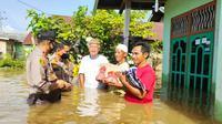 Kapolres Indragiri Hulu menyerahkan bantuan banjir ke rumah warga. (Liputan6.com/M Syukur)