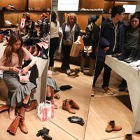 Calon pembeli menjajal sepatu selama Boxing Day di Department stores Selfridges, London, Selasa (26/12). Boxing Day merupakan tradisi hari belanja terbesar tahunan yang dirayakan setiap 26 Desember atau sehari setelah Natal. (Daniel LEAL-OLIVAS/AFP)