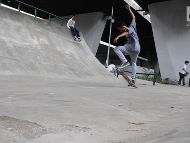 Skater sedang bermain di skaterpark di kolong Flyover Slipi, Jakarta, Selasa (15/1). Belum diresmikan, skaterpark di kolong Flyover Slipi, tampak berberapa dilintasan tampak rusak. (Liputan6.com/Herman Zakharia)