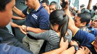 Petugas polisi menggiring tersangka kasus pembunuhan Wayan Mirna Salihin, Jessica Kumala Wongso memasuki pintu penjagaan Rutan Pondok Bambu, Jakarta, Jumat (27/5). Selama dua puluh hari ke depan, Jessica akan dititipkan disana. (Liputan6.com/Yoppy Renato)