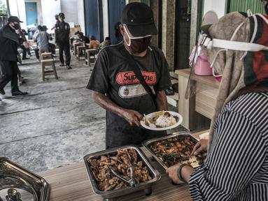 Warga mengambil makanan gratis di Jalan Basuki Rachmat, Cipinang Muara, Jakarta, Senin (8/3/2021). Sejak Juli 2020, Hadi (40) dibantu teman-temannya menggelar layanan makan gratis kepada warga