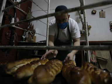 Tukang roti menyiapkan kue di Algiers, Aljazair, Rabu (29/4/2020). Aljazair melonggarkan langkah-langkah karantina akibat virus corona COVID-19 sejak hari pertama bulan suci Ramadan dengan memperpendek jam malam dan memungkinkan beberapa kegiatan komersial. (AP Photo/Toufik Doudou)