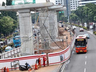 Bus transjakarta melintas di samping proyek LRT di kawasan Kuningan, Jakarta Selatan, Rabu (21/2). Presiden Jokowi meminta semua proyek konstruksi layang (elevated) dihentikan sementara. (Liputan6.com/Immanuel Antonius)