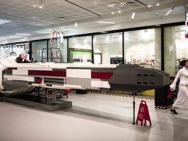 """Pesawat ruang angkasa """"Star Wars X-Wing"""" skala penuh dari balok lego ditampilkan di pusat perbelanjaan pinggiran kota Paris, 12 Desember 2018. Pesawat yang terbuat lebih dari satu juta balok Lego itu untuk memeriahkan perayaan Natal. (Philippe LOPEZ/AFP)"""