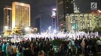 Warga menikmati car free night saat malam pergantian tahun di kawasan Bundaran HI, Jakarta, Senin (31/12). Hujan yang mengguyur Jakarta sejak siang tidak menyurutkan antusias warga menikmaticar free night. (Liputan6.com/Angga Yuniar)