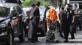 Bupati Banggai Laut, Sulawesi Tengah (Sulteng), Wenny Bukamo dikawal petugas saat tiba di Gedung Merah Putih KPK, Jakarta, Sabtu (5/12/2020). Wenny Bukamo terjerat Operasi Tangkap Tangan (OTT) KPK dalam dugaan kasus suap untuk kepentingan kampanye pemenangan. (Liputan6.com/Herman Zakharia)