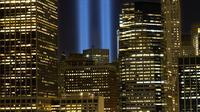 Sorotan cahaya kembar berwarna biru untuk peringati peristiwa serangan 9/11 di Kota New York, Minggu (10/9). Dua cahaya biru tegak lurus itu melambangkan menara kembar WTC yang menjadi sasaran serangan bunuh diri tersebut. (AP Photo/Mark Lennihan)