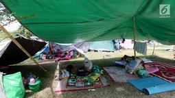 Pengungsi korban gempa dan tsunami Palu beristirahat di tenda pengungsian lapangan Walikota Palu, Sulawesi Tengah, Senin (8/10). Nantinya, pemerintah akan memindahkan pengungsi yang masih bertahan di tenda ke barak pengungsian. (Liputan6.com/Fery Pradolo)