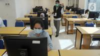 Petugas membagikan kertas pada peserta saat Ujian Tulis Berbasis Komputer (UTBK) gelombang pertama di Kampus Fakultas Teknik UPN Veteran Jakarta, Cinere, Depok, Jawa Barat, Minggu (5/7/2020). UTBK 2020 dibagi dua gelombang, pertama 5-14 Juli 2020 dan kedua 20-29 Juli 2020. (merdeka.com/Arie Basuki)