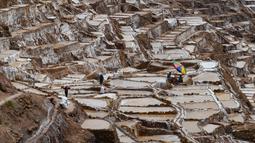 Pekerja beraktivitas di tambak garam di Maras, Peru, 29 April 2019. Tambak garam ini sudah digunakan sejak zaman pra-Inca. (Pablo PORCIUNCULA BRUNE/AFP)