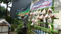 Pedagang mengambil sembako yang digantung di rak kayu sisi jalan di kawasan Rawa Barat, Jakarta Selatan, Kamis (14/5/2020). Selama masa pandemi COVID-19, pihak kelurahan dan masjid sekitar menyediakan paket berisi mi instan, telur, dan masker untuk warga yang membutuhan. (merdeka.com/Imam Buhori)