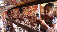 Perajin batik buat motif bertemakan cerita anak guna memperkenalkan batik kepada anak-anak.