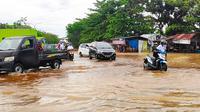Warga mendorong sepeda motor karena mogok akibat nekat melintasi banjir di Pekanbaru. (Liputan6.com/M Syukur)
