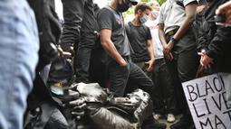 Demonstran merobohkan patung pedagang budak Edward Colston saat protes Black Lives Matter di Bristol, Inggris, Minggu (7/6/2020). Aksi tersebut dilakukan sebagai bentuk protes atas kematian George Floyd saat ditangkap oleh polisi di Amerika Serikat. (Ben Birchall/PA via AP)