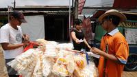 Iman (kanan) bersama Drajat melayani pembeli kerupuk ikan di Jalan Raya Bogor, Depok, Jawa Barat, Rabu (19/10). Menurut Iman, tidak jarang dagangannya habis terjual meski sering pula harus kembali dibawa pulang. (Liputan6.com/Helmi Fithriansyah)