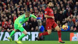 Penyerang Liverpool, Mohamed Salah menggiring bola melewati kiper Everton, Jordan Pickford selama pertandingan Liga Inggris di Anfield Stadium (2/12). Liverpool menang tipis 1-0 atas Everton. (AP Photo / Jon Super)