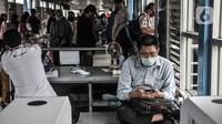 Calon penumpang mengoperasikan telepon genggam di Halte Harmoni, Jakarta, Senin (16/11/2020). Penyediaan fasilitas wifi gratis di halte Transjakarta guna meningkatkan kenyamanan penumpang. (merdeka.com/Iqbal S. Nugroho)