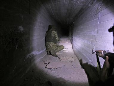Pejuang Suriah dukungan Turki memeriksa terowongan yang diduga dibangun oleh pejuang Kurdi di kota perbatasan Tal Talyyad, Suriah, Senin (21/10/2019). Pasukan Kurdi sepakat untuk menarik diri dari Tal Abyad ke Ras al-Ain. (Bakr ALKASEM/AFP)