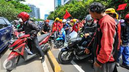 Pengendara motor harus menaiki jalur busway untuk bisa melintas di depan kantor Kemenkes, Jakarta Selatan, Rabu (4/5). Ribuan bidan desa menggelar aksi demo dan menutup akses jalur lambat di depan kantor Kemenkes. (Liputan6.com/Yoppy Renato)