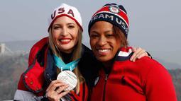 Ivanka Trump dan Lauren Gibbs berpose dengan medali perak selama kejuaraan Olimpiade Musim Dingin Pyeongchang 2018 di depan menara lompat ski di Pyeongchang (25/2). (AFP Photo/Pool/Eric Gaillard)