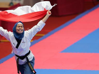 Atlet taekwondo, Defia Rosmaniar, melakukan selebrasi usai berhasil meriah medali emas pertama untuk Indoensia di Asian Games 2018 di JCC, Jakarta, Minggu (19/8/2018). (Bola.com/Peksi Cahyo)