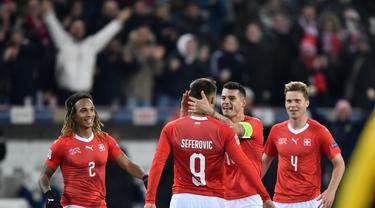 Haris Saferovic dan Granit Xhaka merayakan gol pertama timnas Swiss pada laga Nations League yang berlangsung di stadion Swiss porarena, Senin (19/11). Timnas Swiss menang 5-2. (AFP/Fabrice Coffrini)
