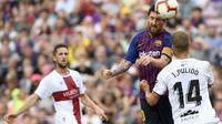 Gelandang Barcelona, Lionel Messi, duel udara dengan bek Huesca, Jorge Pulido, pada laga La Liga Spanyol di Stadion Camp Nou, Barcelona, Minggu (2/8/2018). Barcelona menang 8-2 atas Huesca. (AFP/Lluis Gene)