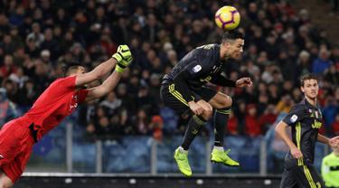 Penyerang Juventus, Cristiano Ronaldo berebut  bola dengan kiper Lazio, Thomas Strakosha pada pekan ke-21 Serie A di Stadion Olimpico, Minggu (27/1). Sempat tertinggal, Ronaldo membawa Juventus menang 2-1 atas Lazio. (AP/Gregorio Borgia)