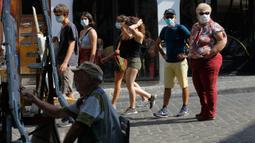 Pelukis terlihat saat turis berjalan-jalan di distrik Montmartre, Paris pada Senin (10/8/2020). Penggunaan masker mulai hari Senin (10/8) diwajibkan di area luar ruangan yang ramai di ibu kota Prancis itu untuk mengendalikan peningkatan tingkat infeksi virus corona. (AP Photo/Michel Euler)