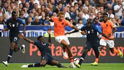 Gelandang Belanda, Memphis Depay, menghindari tekel bek Prancis, Samuel Umtiti, pada laga UEFA Nations League di Stade de France, Paris, Minggu (9/9/2018). Prancis menang 2-1 atas Belanda. (AFP/Franck Fife)