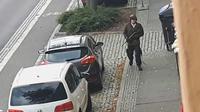 Seorang pria berjalan membawa senjata di jalanan Halle an der Saale, Halle, Jerman, Rabu (9/10/2019). Pelaku melarikan diri menggunakan mobil usai melancarkan aksinya. (Andreas Splett/ATV-Studio Halle/AFP)