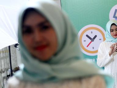 """Model melihat aplikasi muslim berbasis komunitas bernama """"umma"""", Jakarta, Kamis (25/4). Aplikasi dengan fitur penunjang ibadah, konten islami yang dipersonalisasi kecerdasan buatan dan fitur komunitas memiliki misi untuk mempermudah umat muslim Indonesia menjadi khairu ummah. (Liputan6.com/HO/Ading)"""