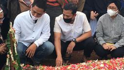 Joko Riyadi (tengah) rekan Markis Kido sesama mantan pebulutangkis PBSI nomor ganda putra menatap haru pusara makam sahabatnya yang harus mendahuluinya terlebih dahulu. (Foto: Bola.com/Erwin Fitriansyah)