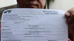 Perwakilan warga dari kasus penipuan perjalanan Travel Agent Hidup Makmur Tentram (HMT) menunjukkan surat di Polda Metro  Jaya, Jakarta, Jumat (10/5). Ratusan orang jemaat batal berangkat ke Yerusalem hingga saat ini belum ada kejelasan untuk berangkat. (merdeka.com/Imam Buhori)