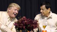 Presiden AS, Donald Trump berbincang dengan Presiden Filipina, Rodrigo Duterte dalam acara makan malam bersama konferensi ASEAN ke-31 di Manila, Minggu (12/11). Trump dan Duterte berbincang mengenai sejumlah isu. (AP Photo/Andrew Harnik)