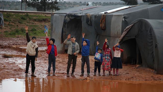 Anak-anak melambaikan tangan dekat tenda pengungsian mereka yang kebanjiran di Kamp Cordoba, Batabu, Idlib, Suriah, Rabu (16/1). Hujan badai membuat kamp pengungsian mereka kebanjiran. (Aaref Watad/AFP)
