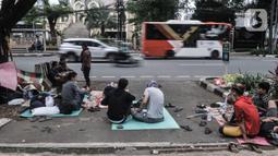 Kendaraan melintas di dekat imigran pencari suaka yang menghuni di depan Kantor UNHCR Kebon Sirih, Jakarta, Kamis (1/4/2021). Puluhan imigran dari berbagai negara konflik kembali menghuni di depan Kantor UNHCR Kebon Sirih sejak beberapa waktu lalu. (merdeka.com/Iqbal S Nugroho)