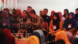 Presiden Joko Widodo berbincang dengan Mensos Agus Gumiwang Kartasasmita saat menyalurkan bansos Program Keluarga Harapan (PKH) dan Bantuan Pangan Non Tunai (BPNT) kepada seribu warga Depok, Jawa Barat, Selasa (12/2). (Liputan6.com/Herman Zakharia)